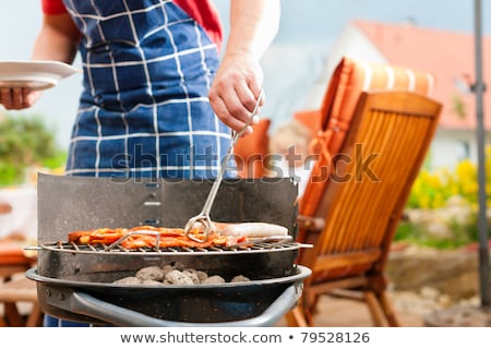 Man with sausages next to barbecue Stock photo © IS2