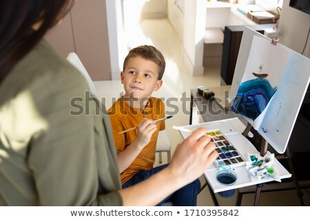 Mother holding baby in front of easel Stock photo © IS2