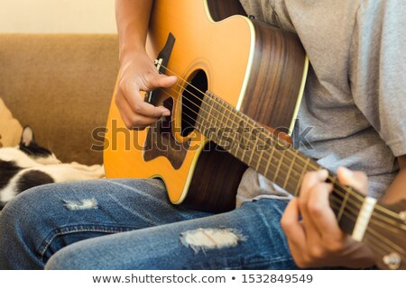 Young man sitting on bench and playing acoustic guitar  Stock photo © manaemedia