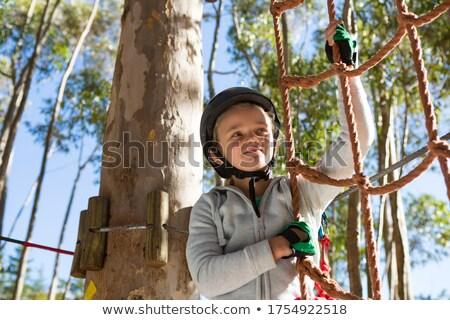 Little girl wearing helmet getting ready to climb on rope fence Stock photo © wavebreak_media