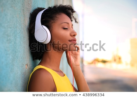 portrait of a smiling young girl listening to music stock photo © deandrobot