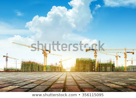 Crane and building construction site against blue sky stock photo © AlisLuch