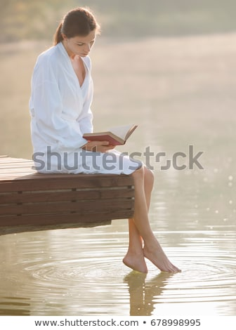 Woman reading and dangling feet in lake Stock photo © IS2