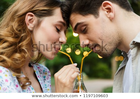 Stock photo: Happy young loving couple outdoors in park having fun drinking soda together.