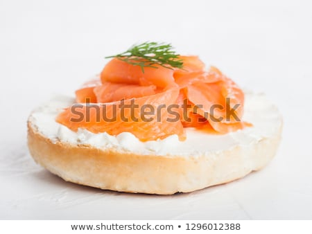 Fresh healthy bagel sandwich with salmon, ricotta and glass of milk on light kitchen table backgroun Stock photo © DenisMArt