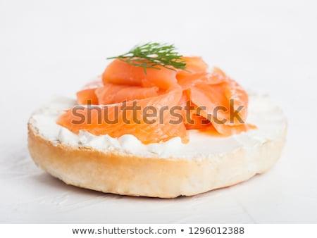 fresh healthy bagel sandwich with salmon ricotta and glass of milk on light kitchen table backgroun stock photo © denismart