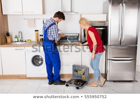 young repairman examining induction stove stock photo © andreypopov