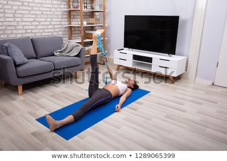 Woman Using Yoga Belt While Doing Exercise Stock photo © AndreyPopov