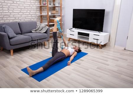 woman using yoga belt while doing exercise stock photo © andreypopov