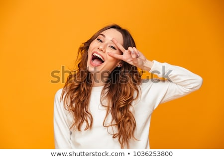 happy young woman standing showing peace gesture and looking at camera stock photo © ichiosea