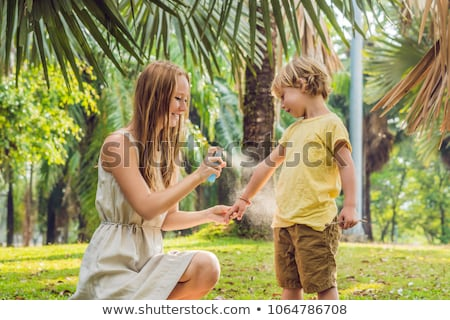 Photo stock: Mom And Son Use Mosquito Sprayspraying Insect Repellent On Skin Outdoor