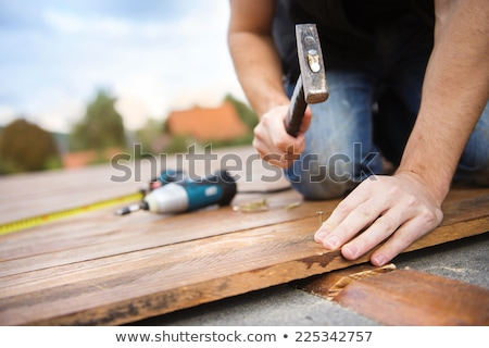 handyman nailing wooden plank with hammer Stock photo © 3dmask