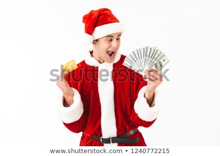 Image of ecstatic man 30s in santa claus costume holding dollar  Stock photo © deandrobot