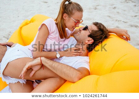 Young Couple Sitting On Hammock Kissing At Beach Stock photo © AndreyPopov