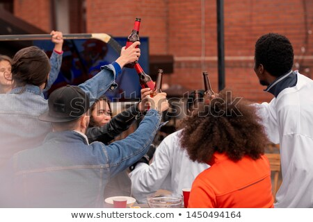 Group of excited hockey fans clinking with bottles of beer after match Stock photo © pressmaster