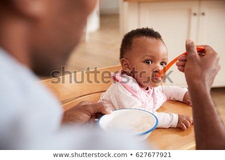 father feeding baby sitting in highchair at home Stock photo © dolgachov