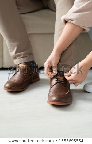 Hands of careful young daughter helping her sick father with shoelaces on boots Stock photo © pressmaster
