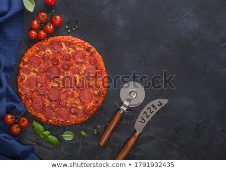 Fresh round baked Hot and Spicy Pepperoni pizza with knife and tomatoes with basil on black backgrou Stock photo © DenisMArt