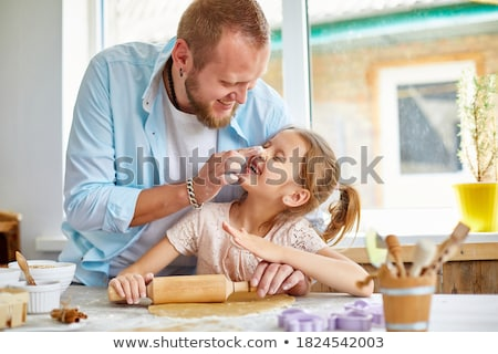 Happy family, father and daughter roll out cookie dough in a kitchen at home. Stock photo © Illia