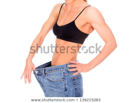 woman with strong abs shows her old big jeans Stock photo © Nobilior