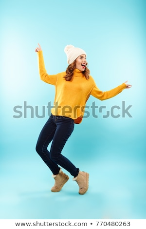 Full-length portrait of a young smiling woman in style clothes standing on gray background Stock photo © deandrobot