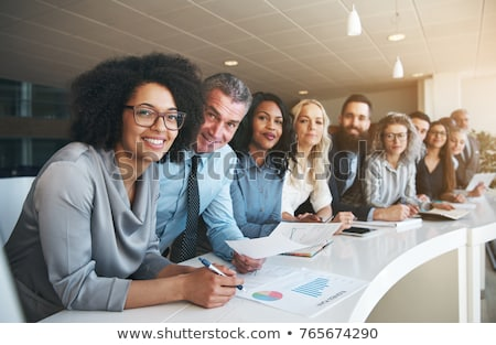 group of a smiling businesspeople standing together in office stock photo © deandrobot