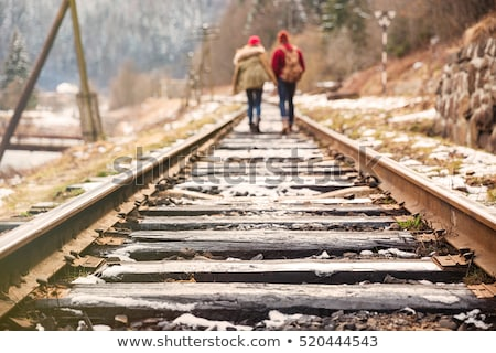 couple walking far away on railroad together stock photo © deandrobot