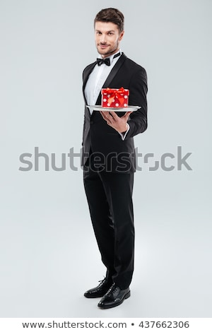 Butler in tuxedo standing and holding tray with gift box Stock photo © deandrobot
