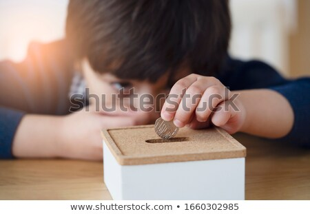 Boy holding coins for money box Stock photo © lovleah