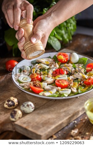 Delicious natural salad with fresly picked green vegetables, chicken meat, quail eggs in a gray plat Stock photo © artjazz