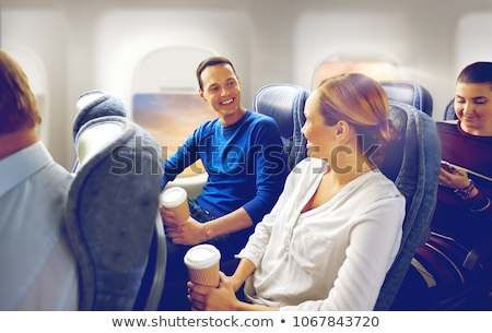 happy passengers with coffee talking in plane Stock photo © dolgachov