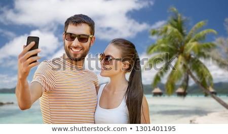 woman taking selfie by smartphone on bora bora stock photo © dolgachov