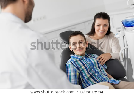 mother and son visiting dentist at dental clinic Stock photo © dolgachov