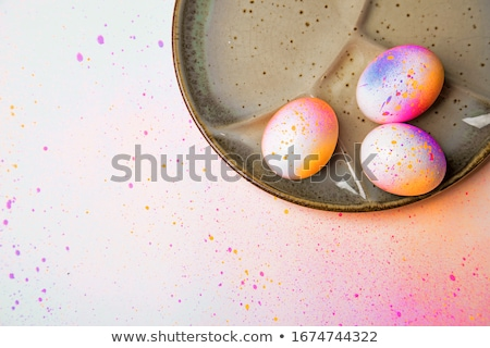Blue and violet Easter eggs on a ceramic plate in a color of Living Coral Pantone on a gray stone ba Stock photo © artjazz