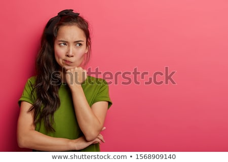Young pensive or discontent woman keeping one hand by chin Stock photo © pressmaster
