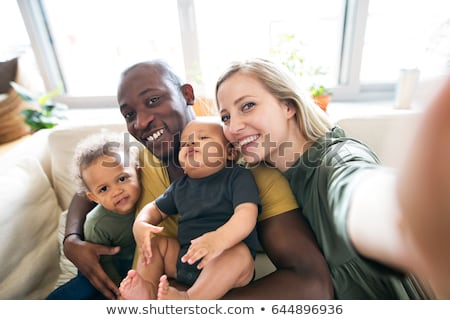 mixed race family with baby taking selfie at home stock photo © dolgachov