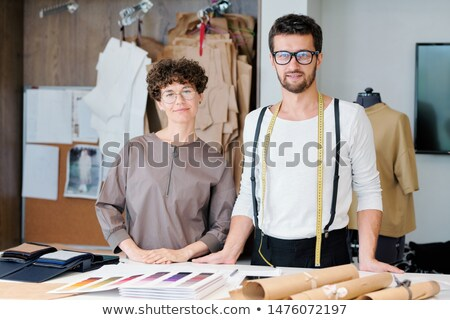 Two young confident designers of new fashion collection doing their usual work Stock photo © pressmaster