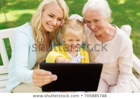 daughter with tablet pc and senior mother at park stock photo © dolgachov