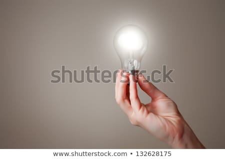 hand holding shiny light bulb stock photo © ra2studio