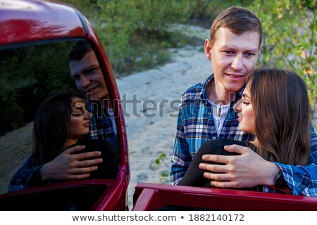 loving couple outdoors at beach near car hugging stock photo © deandrobot