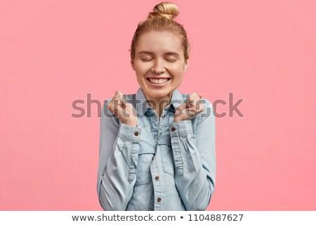 Joyful female with pleasant smile, keeps hands in fists, wears braces on teeth, has dark straight ha Stock photo © vkstudio