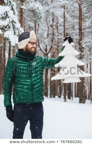 Vertical portrait of dlightful positive bearded male dressed in warm winter clothes, looks with happ Stock photo © vkstudio