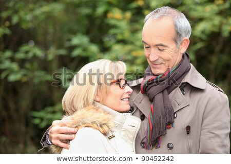 old couple wearing warm clothes in the forest and expressing tenderness stock photo © photography33