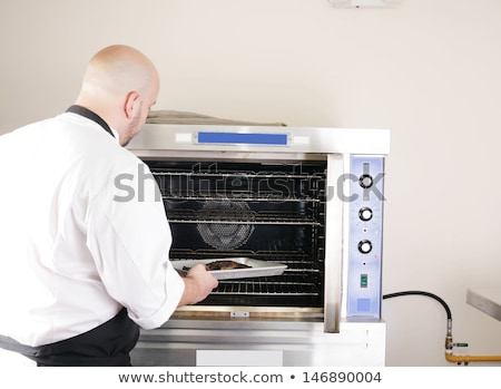 chef putting a tray of a juicy steak in a professional oven Stock photo © dacasdo