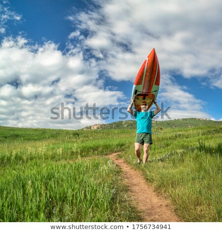 senior paddler carrying paddleboard stock photo © pixelsaway