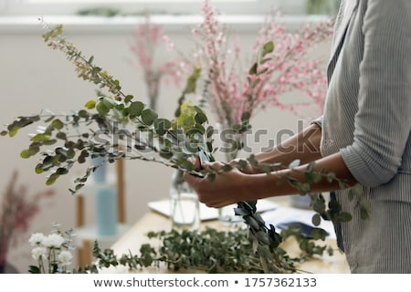 tender female gardener working with plants and flowers stock photo © deandrobot