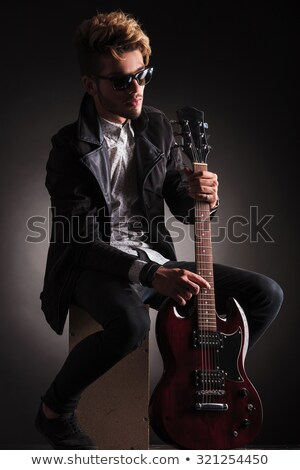 rocker in black leather jacket posing seated in dark studio Stock photo © feedough