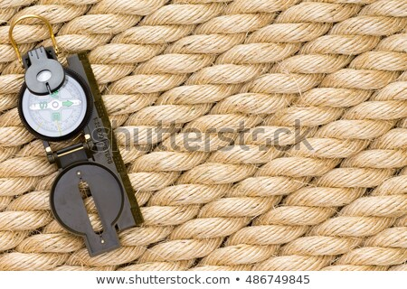 Single nautical compass over thick rope background Stock photo © ozgur