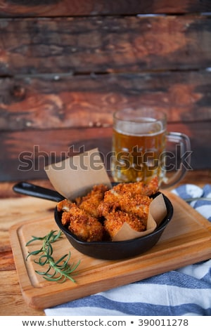 a plate of fresh hot crispy fried chicken with red sause on a stock photo © yatsenko