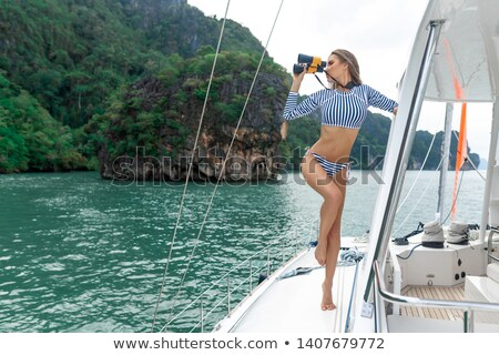 gorgeous woman wearing hat standing on the yacht stock photo © deandrobot